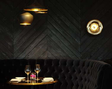 This chic balck velvet tufted banquette with gold lighitng and accents and a rustic chevron wood wall is quite a sexy setting for dinner for two