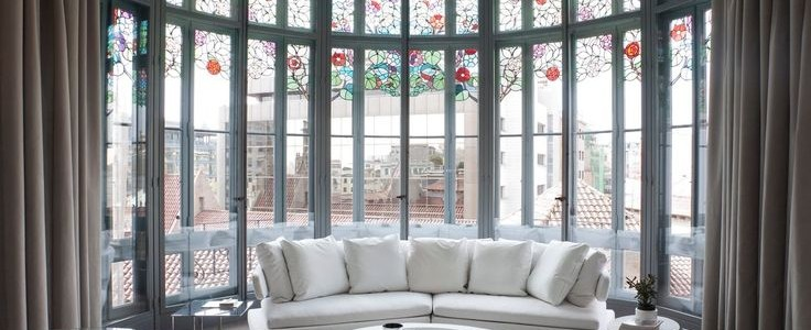 El Palauet Living allows the incredible stain glass windows to steal the show in the design ofthsi chic living room